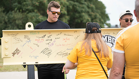 Alumni sign a beam that will be placed in UMBC's new state-of-the-art Events Center.