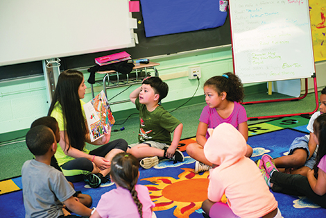 A UMBC STUDENT TEACHER READS TO LAKELAND ELEMENTARY SCHOOL STUDENTS.