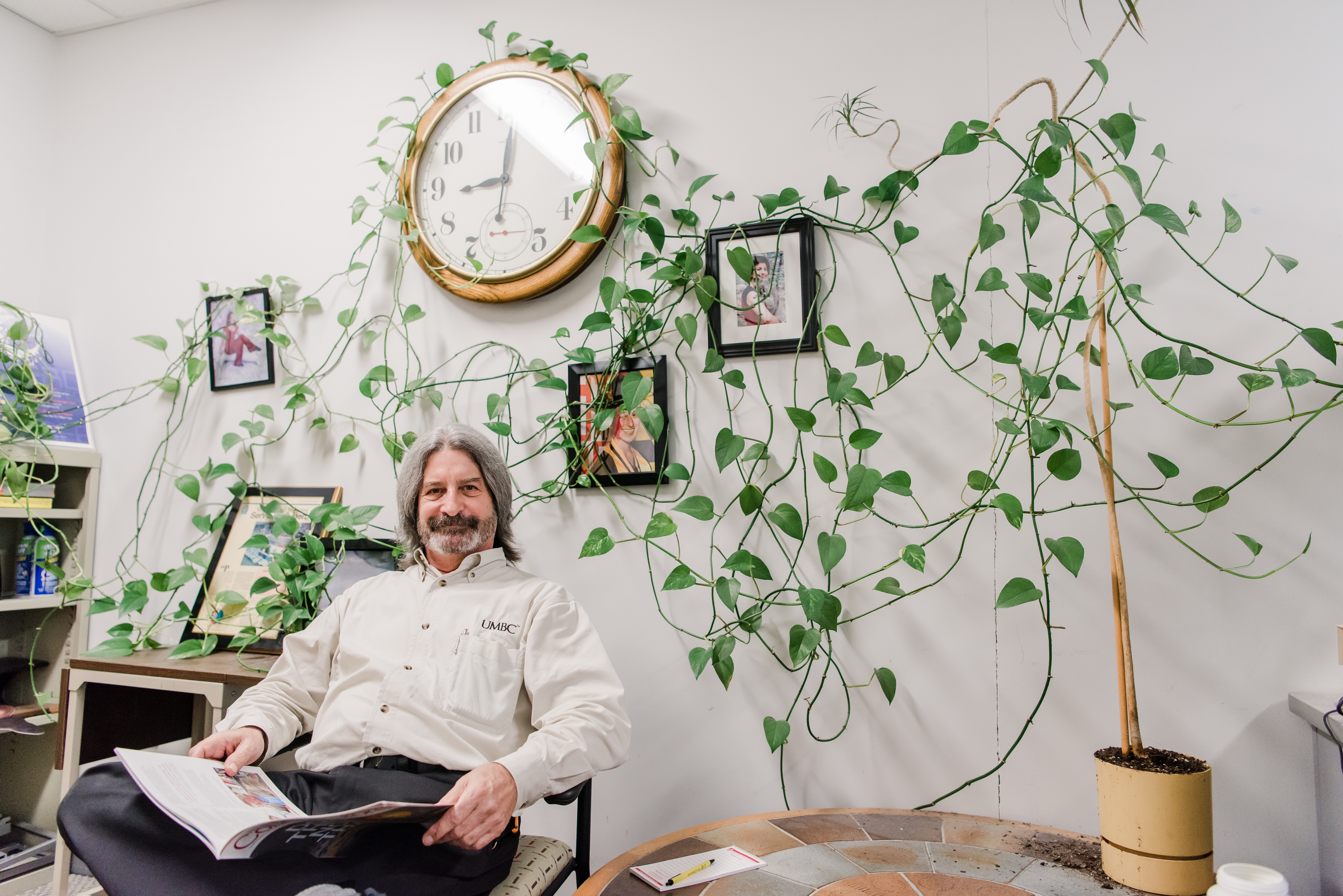 """""""Bookstore Bob"""" Somers with his famous office plant. This and header image by Marlayna Demond '11 for UMBC Magazine."""