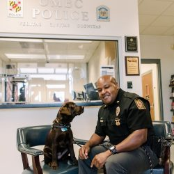 Sergeant Cheatem smiles at the camera as UMBC Police comfort dog looks at him