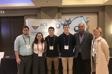 Ram Mohan and team stand in front of American Chemical Society poster