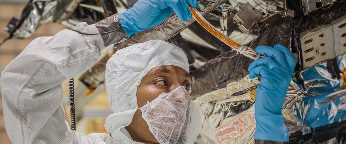 Man in electrical PPE adjusts wires on a satellite