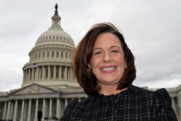 Sarah Butts smiling in a suit jacket in front of the U.S. Capitol