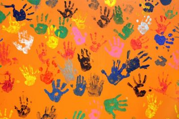 Different colored handprints decorate an orange wall