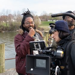 Jovan James and film crew stands on dock