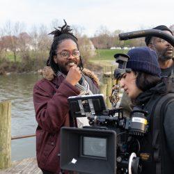 Jovan James and film crew stands on dock