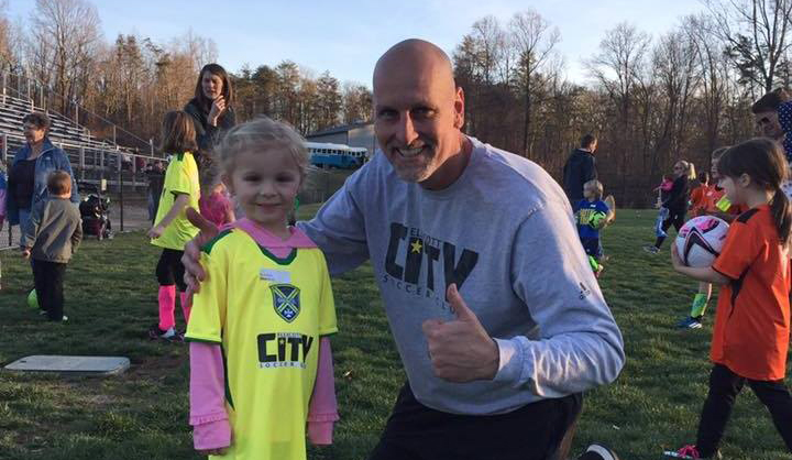 Tim Ryerson gives a thumbs up while posing with a child soccer player