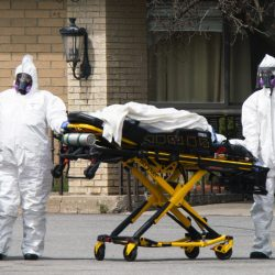 Two EMTs dressed in full PPE wheel out a gurney on the street