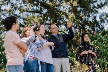 Kevin Omland points towards birds as students look on with binoculars