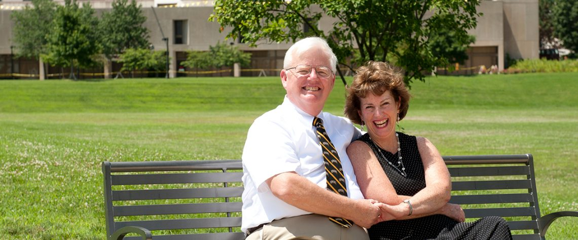 Jim and Kathy Kruger hold hands and smile on a bench outside UMBC's library