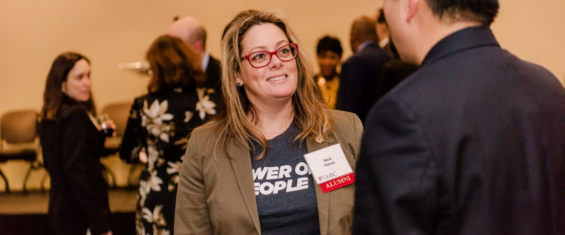 "Nicki Focco, wearing a shirt that reads ""Power of the People,"" talks with man at a reception"