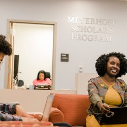 Woman sits on her laptop in the Meyerhoff Scholars Program lounge