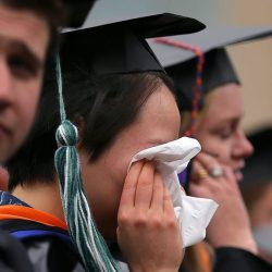 A woman in a graduation cap and gown wipes her eyes with a tissue