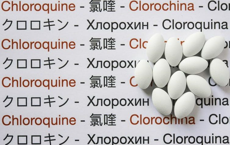 """Pills sit on a background of the word """"Chloroquine"""" in different languages"""