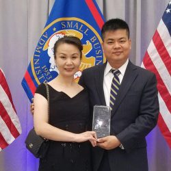 Man and woman hold award with U.S. flags in the background