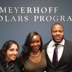 Kizzmekia Corbett, Akanksha Raja Lewis and Nnamdi Osia in front of Meyerhoff Scholars Program sign