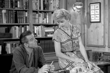 "Scene from sitcom ""Leave It to Beaver"" showing Beaver and his wife in his study"