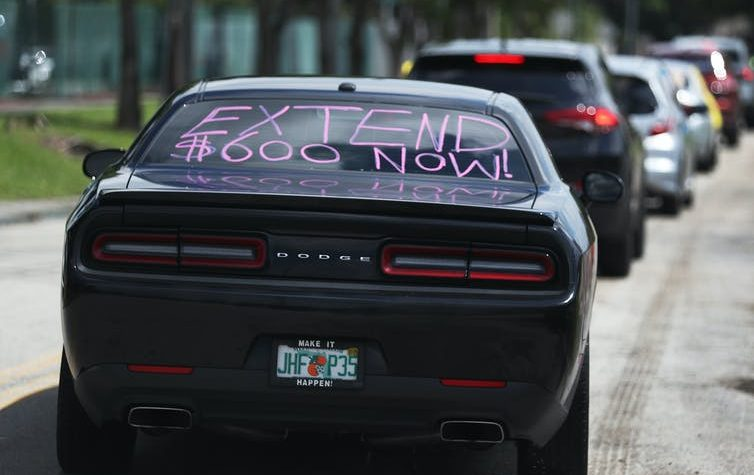 "Black Dodge car with ""Extend $600 now!"" painted on its back windshield"