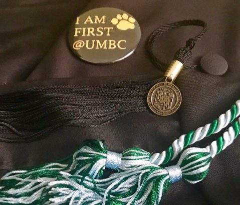 "pin reading ""I am first at UMBC,"" graduation tassel and cord"