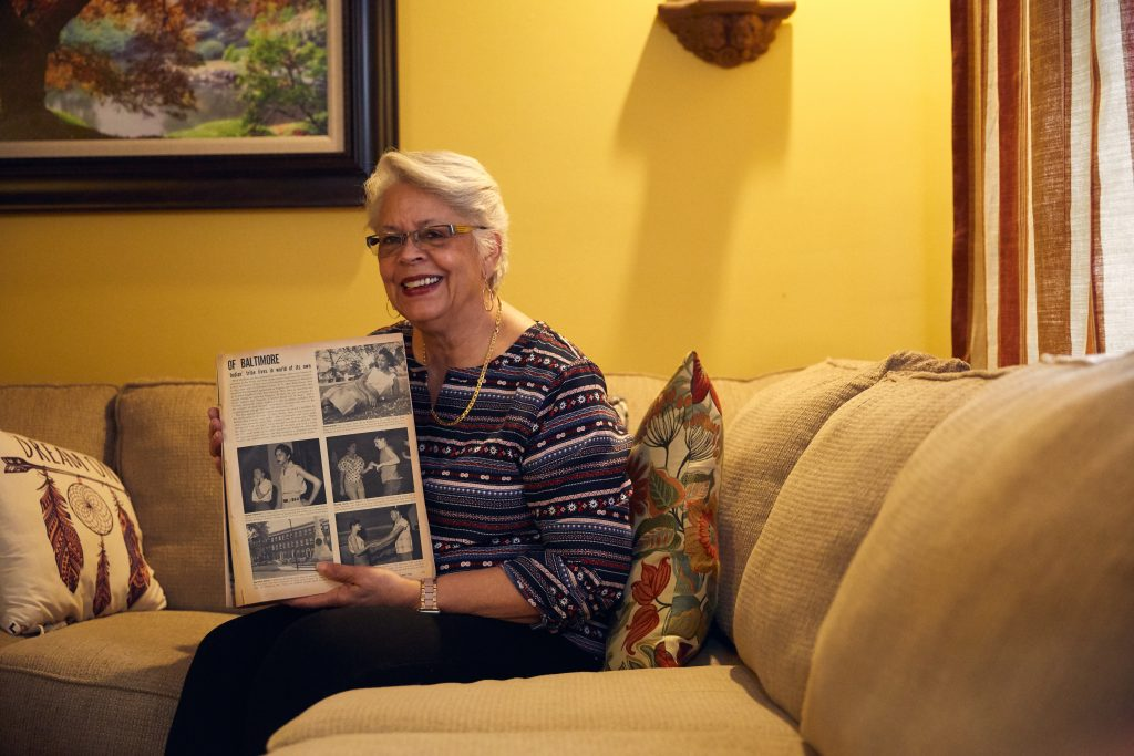 a woman on a couch holding of book of photos