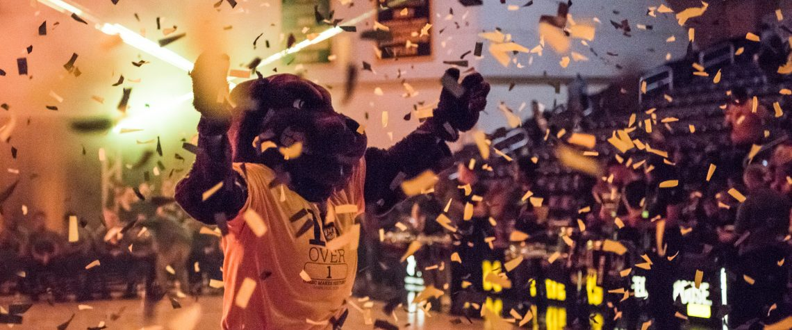 UMBC mascot True Grit stands on the Event Center basketball court as black and gold confetti rains down.