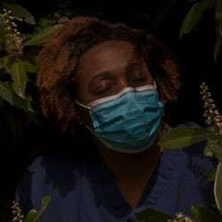 a nurse in a surgical face mask stands in nature