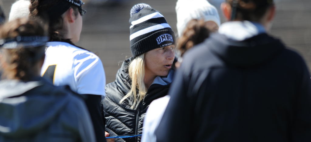 Amy Slade in a winter UMBC hat surrounded by women's lacrosse players.