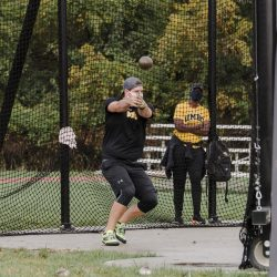 Andrew Haberman throwing the hammer as coach Davina Orieukwu watches