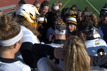 The UMBC women's lacrosse team huddle around coach Amy Slade during a game