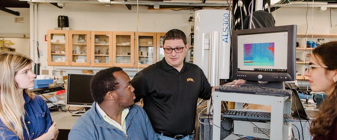 Ruben Delgado, instructs three students in his lab
