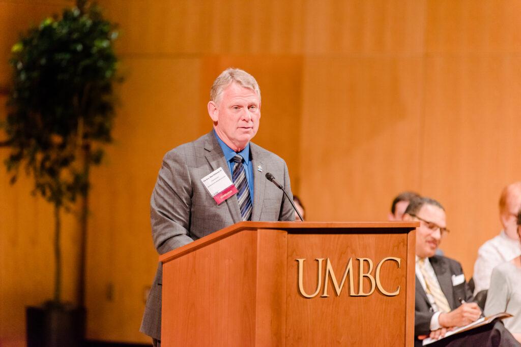 Alan Kittleman stands at a podium that says UMBC