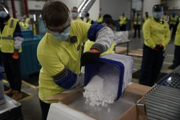 A worker pours dry ice into boxes containing Pfizer's COVID-19 vaccine.