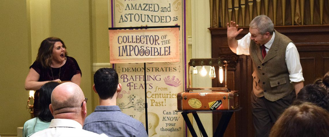 a magician performs in front of an audience with lightbulbs as a trick