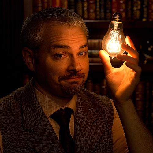 a magician holds a lighted lightbulb