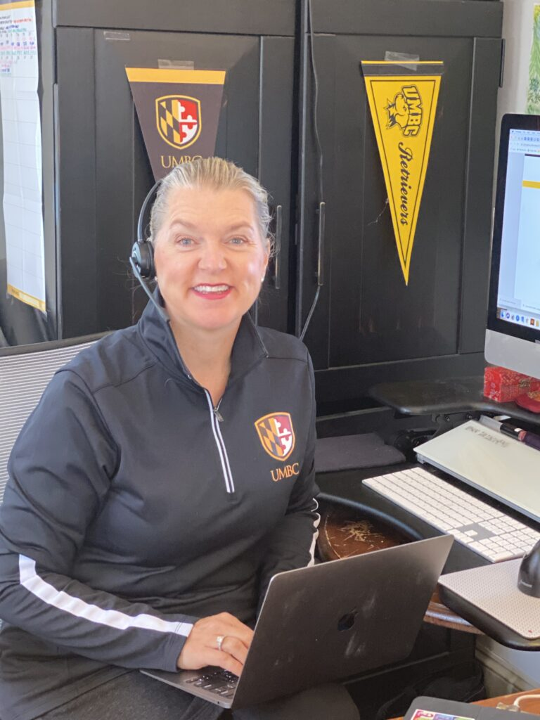 A woman sits at her desk with a laptop on her lap and black and gold gear around her.